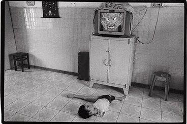 Un ni�o que naci� sin brazos ve la televisi�n en Saig�n. Foto: James Nachtwey